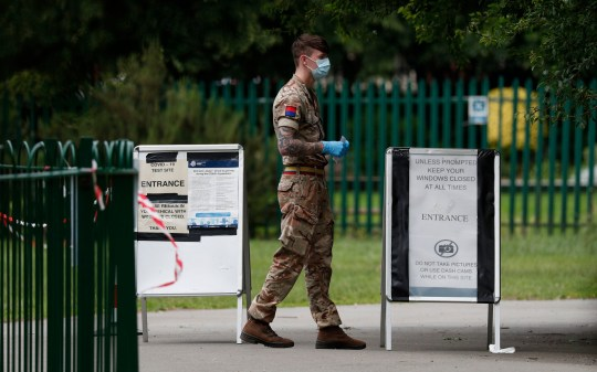 LEICESTER, ENGLAND - JUNE 28: A member of the Military stands at the gate of a walk-in mobile Covid-19 testing centre in Spinney Hill Park on June 28, 2020 in Leicester, England. In a television appearance on Sunday, British Home Secretary Priti Patel confirmed the government was considering a local lockdown after a spike in coronavirus cases in the city. (Photo by Darren Staples/Getty Images)