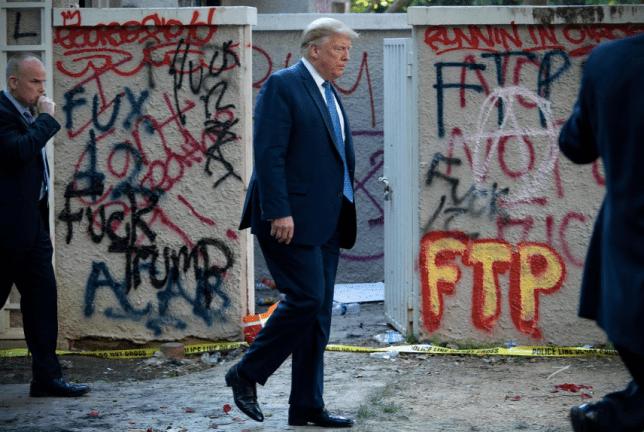 Photo of Donald Trump walking past vandalized church