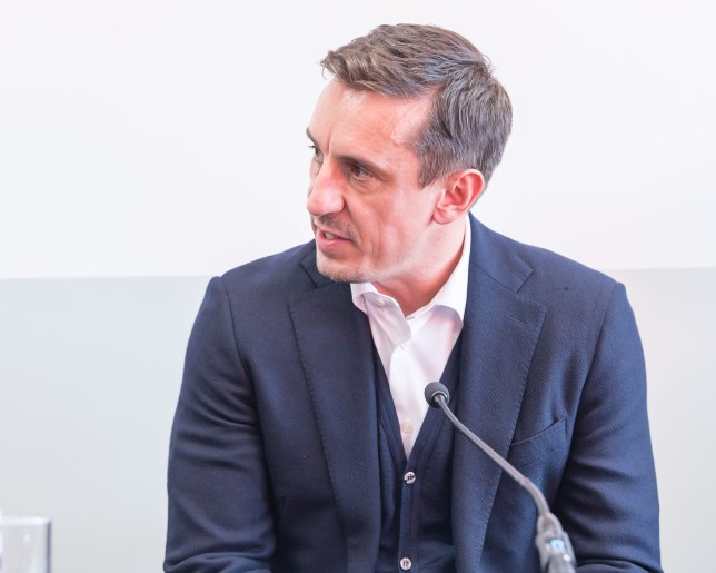 Former Man United footballer Gary Neville wearing a blue suit and white shirt sitting in front of a microphone