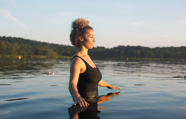 One young mixed race woman standing in lake