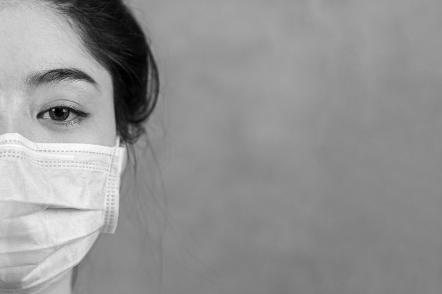 A woman wearing a protective surgical mask.