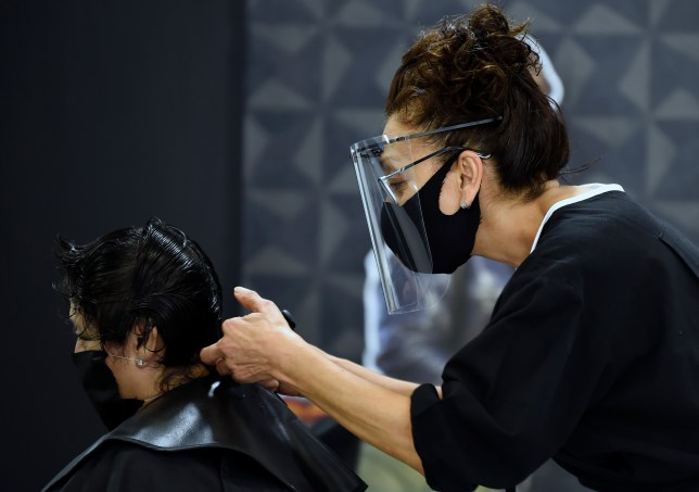 A client gets a haircut at a beauty salon, during the COVID-19 pandemic.