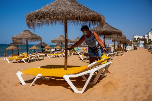 a worker washing an umbrella on a beach in the algarve