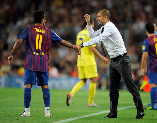 Barcelona's coach Josep Guardiola gives Thiago instructions