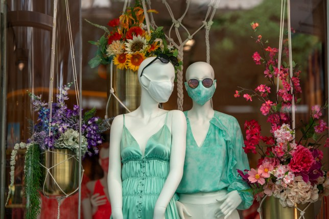 Two mannequins are seen wearing masks.