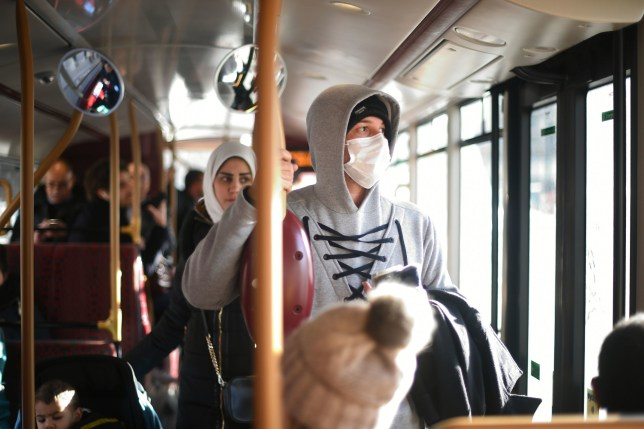 A pedestrian wears a protective facemask while taking a bus in Westminster, London