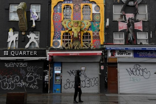 A man walks past a row of closed shops in Camden