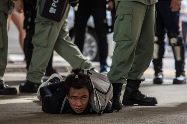Riot police detain a man as they clear protesters taking part in a rally in hong kong
