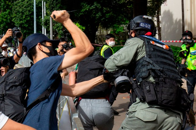 A protester uses a sharp object against a police officer