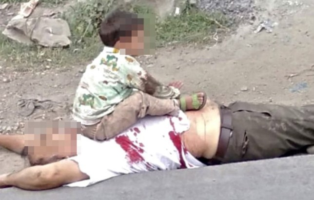 Picture of toddler sitting on his dead grandfather's body in the  Sopore town of Indian-administered Kashmir