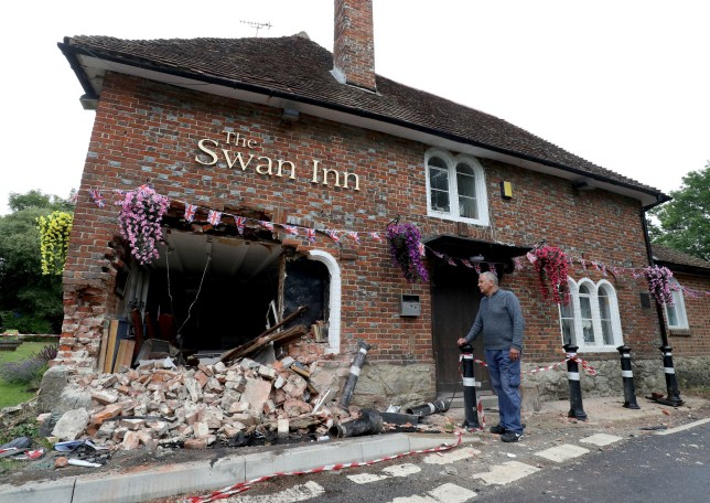 Ray Perkins, landlord of the Swan Inn in Ashford, Kent, looks at the damage to his pub after a car crashed into it