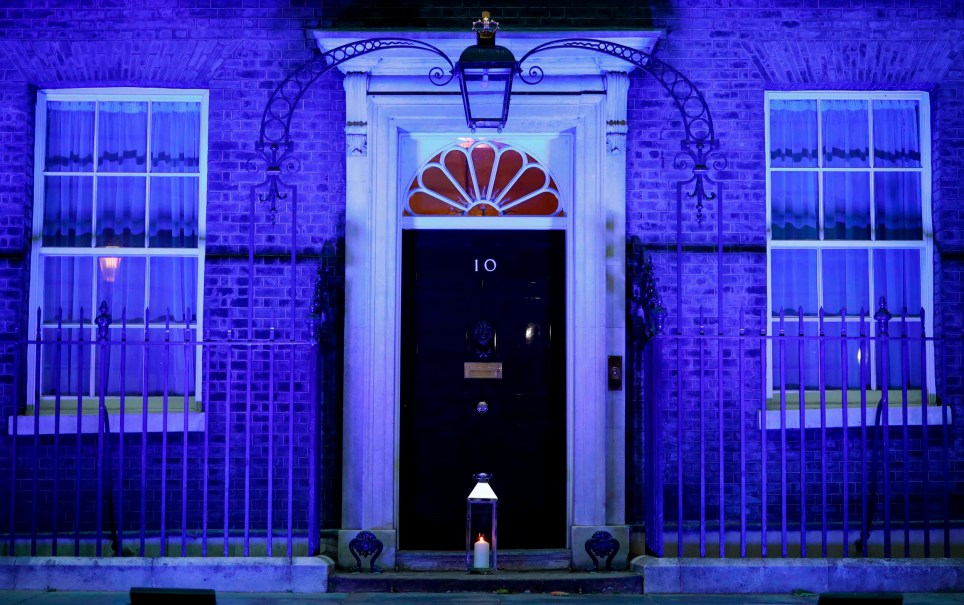 A candle is lit and placed on the doorstep of 10 Downing Street in central London on July 4, 2020 in honour of the tens of thousands of people who have died as a result of the coronavirus pandemic in the UK as the building itself is lit up blue as a tribute to NHS workers and to mark the 72nd anniversary of the NHS. (Photo by Tolga Akmen / AFP) (Photo by TOLGA AKMEN/AFP via Getty Images)