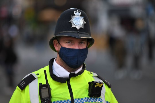 A police officer wearing a protective face covering patrols in Soho in London on July 5, 2020, as the Soho area embraces pedestrianisation in line with an easing of restrictions during the novel coronavirus COVID-19 pandemic. - Pubs in England reopened this weekend for the first time since late March, bringing cheer to drinkers and the industry but fears of public disorder and fresh coronavirus cases. (Photo by DANIEL LEAL-OLIVAS / AFP) (Photo by DANIEL LEAL-OLIVAS/AFP via Getty Images)