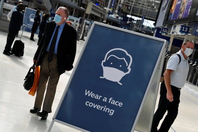 Workers wearing face-masks are seen travelling through Waterloo Station