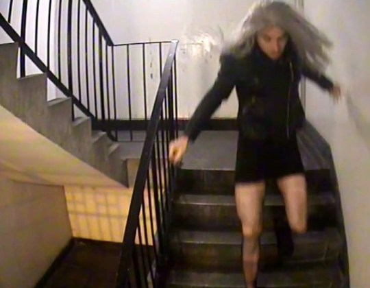 Sex offender Mark Brown racing down a set of stairs wearing a silver wig in order to carry out an attack on his victim