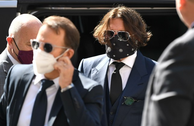 Hollywood actor Johnny Depp (3R), wearing a face mask or covering due to the COVID-19 pandemic, arrives on the first day of his libel trial against News Group Newspapers (NGN), at the High Court in London, on July 7, 2020. - A libel trial was due to begin on Tuesday between Hollywood actor Johnny Depp and a British tabloid newspaper over claims that he was violent to his former wife, Amber Heard. (Photo by DANIEL LEAL-OLIVAS / AFP) (Photo by DANIEL LEAL-OLIVAS/AFP via Getty Images)
