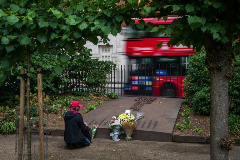 A man lays a floral tribute on the Tavistock Square Garden Memorial, near to where a bomb was detonated on a bus killing 13 people, as events are held to mark the fifteenth anniversary of the London bombings