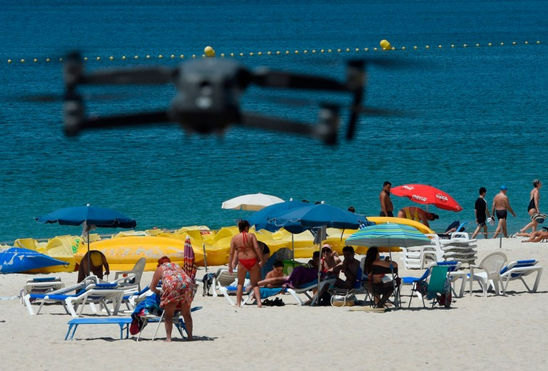 A drone flown by local police warns people to respect social distancing and safety measures to avoid any fresh coronavirus outbreaks at the Areas beach in Sanxenxo, northwestern Spain