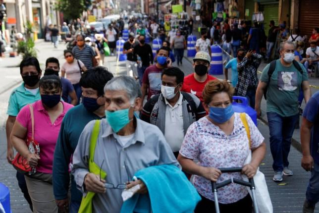 Les gens attendent en ligne le long de la rue avant d'entrer dans la zone où les magasins sont ouverts, lors de la réouverture progressive des activités commerciales dans la ville, alors que l'épidémie de maladie à coronavirus (COVID-19) continue, à Mexico, Mexique, le 14 juillet 2020. REUTERS / Henry Romero