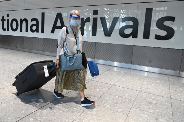 Passengers wearing a face mask or covering due to the COVID-19 pandemic, arrive at Heathrow airport, west London, on July 10, 2020. - The British government on Friday revealed the first exemptions from its coronavirus quarantine, with arrivals from Germany, France, Spain and Italy no longer required to self-isolate from July 10. Since June 8, it has required all overseas arrivals -- including UK residents -- to self-quarantine to avoid the risk of importing new cases from abroad. (Photo by DANIEL LEAL-OLIVAS / AFP) (Photo by DANIEL LEAL-OLIVAS/AFP via Getty Images)