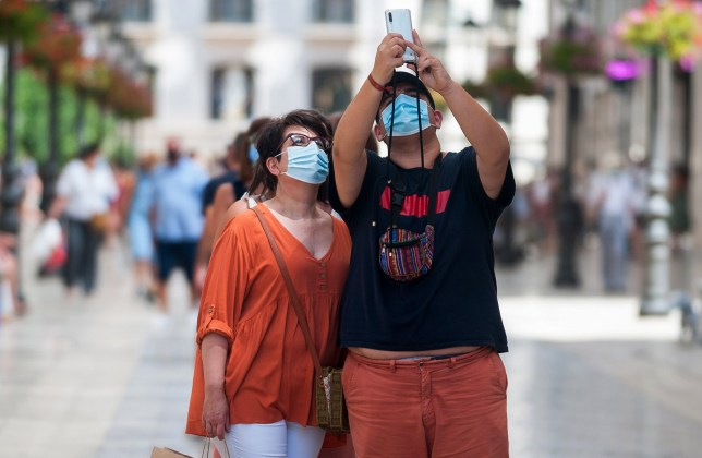 Mandatory Credit: Photo by Jesus Merida/SOPA Images/REX (10713022b) People wearing face masks taking a selfie in the middle of 'Marques de Larios' street during the first day of mandatory use of face masks. New coronavirus infections in Spain after the easing of restrictions have caused the regional government to impose the obligatory use of face masks in outdoors and closed places and beaches, even when they observe a safe distance between people. This measure tries to curb the spread of the coronavirus pandemic. Face mask mandate in Malaga, Spain - 15 Jul 2020