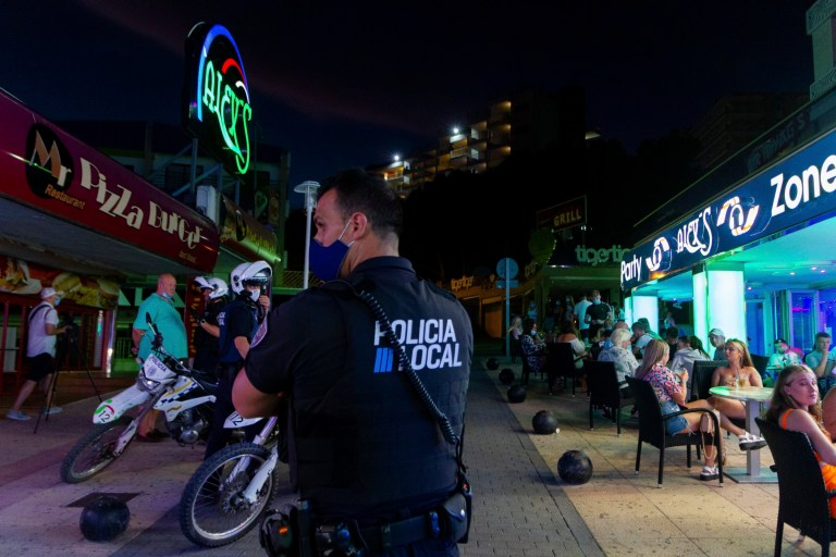 A police officer patrols as tourists stand in a terrace at the resort of Magaluf on the Spanish Balearic island of Mallorca, Spain, Thursday, July 16, 2020. Authorities in Spain's Balearic Islands are pulling the plug on endless drunken nights to the beat of techno music by closing bars and nightclubs in beachfront areas popular with young and foreign visitors. (AP Photo/Francisco Ubilla)