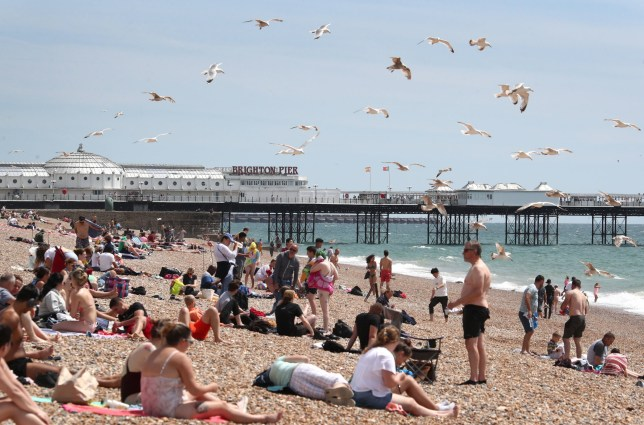 People enjoy the sunshine and warm weather on Brighton Beach. PA Photo. Picture date: Saturday July 18, 2020. Photo credit should read: Gareth Fuller/PA Wire
