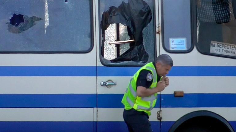 Un policier, qui a apporté de l'eau pour les otages contenus dans un bus après qu'un homme armé a saisi le bus longue distance et pris une dizaine de personnes en otage, réagit après un coup de feu que l'assaillant a envoyé pour l'éloigner dans le centre-ville de Loutsk, à quelque 400 kilomètres (250 miles) à l'ouest de Kiev, en Ukraine, le mardi 21 juillet 2020. L'assaillant est armé et transportant des explosifs, selon un communiqué de la police ukrainienne sur Facebook.  Les policiers essaient d'entrer en contact avec l'homme et ils ont bouclé la zone.  (Bureau de presse de la police ukrainienne via AP)