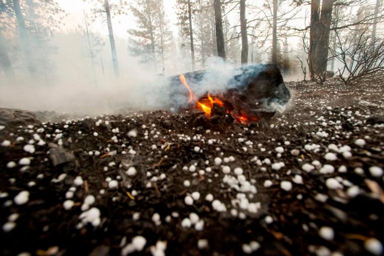Une bûche continue de brûler alors que la grêle tombe directement sur l'incendie de Hog près de Susanville, en Californie, le 21 juillet 2020. - Une cellule d'orage mélangée à une colonne de cendres de pyrocumulus du feu de Hog, entraînant des vents erratiques et des éclairs avant de se transformer en une tempête de grêle qui a éteint une partie de l'incendie.