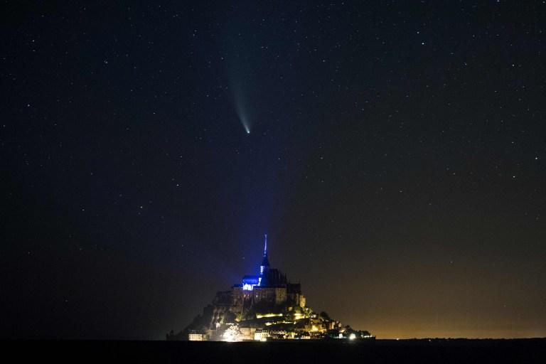 TOPSHOT - Cette photo longue exposition prise le 22 juillet 2020, montre une vue de la comète NEOWISE (C / 2020 F3) dans le ciel au-dessus du Mont-Saint-Michel, ouest de la France. - La Comète C / 2020 F3 a été découverte le 27 mars 2020 par NEOWISE, le Near Earth Object Wide-field Infrared Survey Explorer, qui est un télescope spatial lancé par la NASA en 2009. (Photo par Loic VENANCE / AFP) (Photo par LOIC VENANCE / AFP via Getty Images)