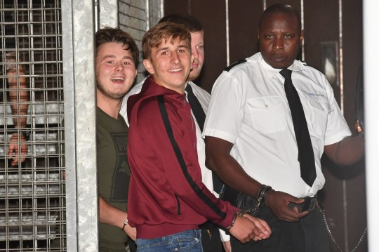 Defendants grinning as they leave court iin handcuffs