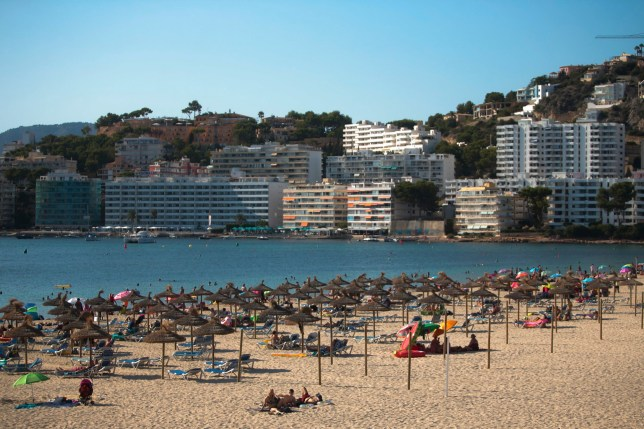 Sunbathers enjoy the beach in Palma de Mallorca, Spain, Sunday, July 26, 2020.