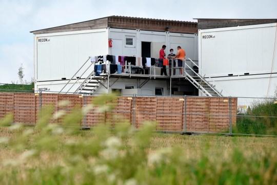 Les travailleurs saisonniers agricoles se tiennent à l'extérieur des conteneurs d'hébergement qui sont protégés du monde extérieur avec une clôture le 27 juillet 2020 à Mamming, dans le sud de l'Allemagne, après qu'une épidémie de cas de coronavirus COVID-10 se soit élevée.  - Au moins 174 travailleurs saisonniers ont été testés positifs pour le virus sur la ferme de la municipalité de Mamming, la plupart originaires de Hongrie, de Roumanie, de Bulgarie et d'Ukraine, et quelque 500 travailleurs ont été envoyés en quarantaine sur la ferme bavaroise ce week-end pour contenir une épidémie massive de coronavirus.  (Photo par Christof STACHE / AFP) (Photo par CHRISTOF STACHE / AFP via Getty Images)