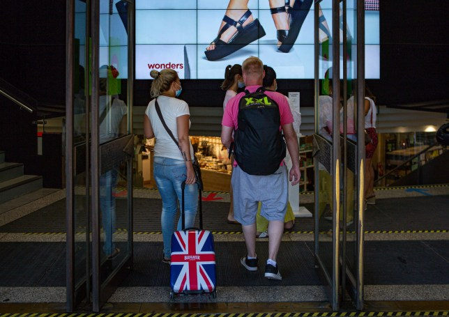 epa08568609 A British couple enter a shop in downtown in Barcelona, Spain, 27 July 2020, a day after the first day of the UK imposed surprise 14-day quarantine to those people arriving from Spain due to a surge in coronavirus cases. EPA/Enric Fontcuberta