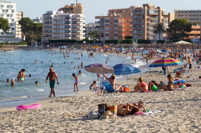 Tourists sunbathe at Palmanova Beach on the Island of Mallorca on July 27, 2020.
