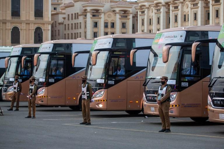 Les agents de sécurité se tiennent devant les bus qui transportent les pèlerins se dirigeant vers la Meeqaat pour le pèlerinage du hajj