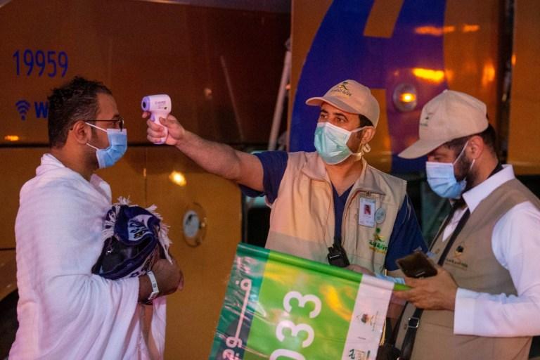 Un agent de santé vérifie la température d'un pèlerin musulman se dirigeant vers le Meeqaat ahed du hajj