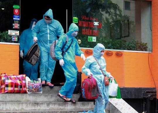 Des gens marchent vers une ambulance pour être conduits à un hôpital pour mise en quarantaine lié à un cas présumé de COVID-19 à Hanoi, Vietnam, mercredi 29 juillet 2020. Le Vietnam intensifie les mesures de protection en raison du nombre de transmissions locales, à partir d'un hôpital du ville balnéaire populaire de Da Nang, ne cesse d'augmenter depuis le week-end.  (Photo AP / Hau Dinh)