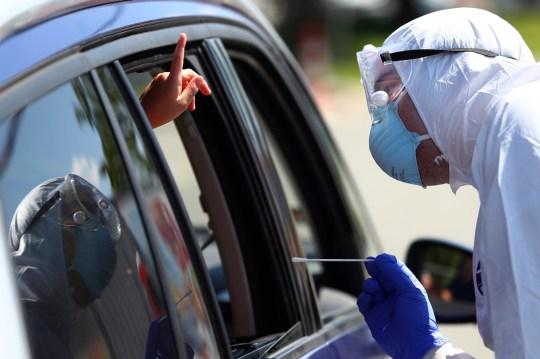 Un enfant fait des gestes avant qu'un personnel médical prélève un échantillon pour un test volontaire de maladie à coronavirus (COVID-19) à la nouvelle station de test corona de la station-service `` Hochfelln '' sur l'autoroute A8 entre Salzbourg et Munich près de Bergen, en Allemagne, jeudi, 30 juillet 2020.