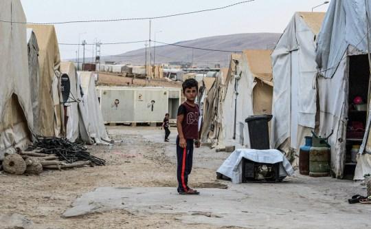 Un garçon se tient dans une ruelle entre des tentes dans un camp de personnes déplacées à l'intérieur du pays (PDI) de la minorité yézidie de l'Iraq je