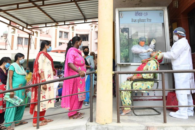 Health officials collect a nasal swab sample from a woman to test for the COVID-19 coronavirus, at a civil hospital in Amritsar on July 31, 2020.