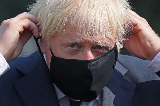 Prime Minister Boris Johnson puts on a face mask at the Northern Ireland Ambulance Service HQ