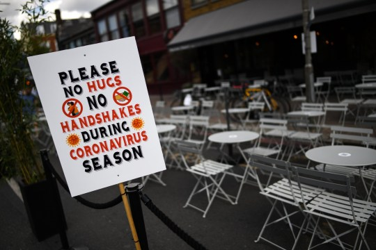 A sign reading 'Please No Hugs, No Handshakes, During Coronavirus season' is seen outside a restaurant in Clapham on August 2, 2020 in London, England.
