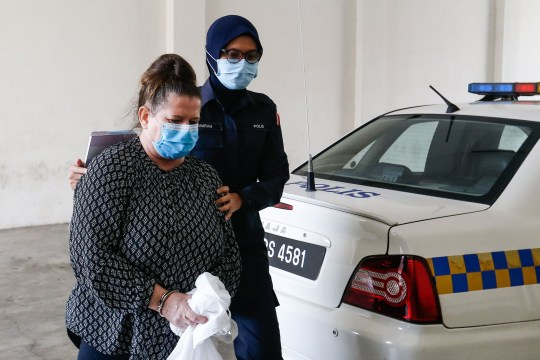 British national Samantha Jones (L), accused of killing her husband in 2018, is escorted by a police officer as she arrives at a court in Alor Setar, in northern Malaysia, on August 3, 2020.
