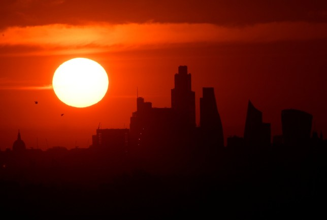The sun rises behind the skyline of St Paul's Cathedral