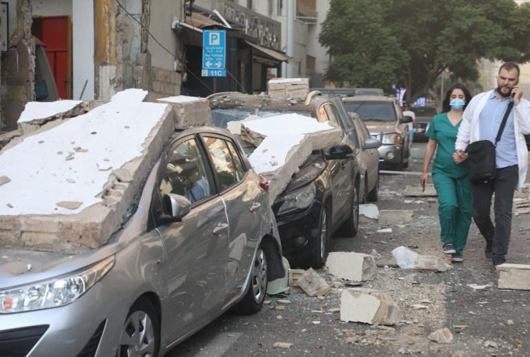 Crédit obligatoire: Photo de Xinhua / REX (10733107i) Des personnes passent devant des véhicules endommagés après l'explosion à Beyrouth, au Liban, le 4 août 2020. Les deux énormes explosions qui ont secoué la capitale libanaise Beyrouth mardi ont fait des dizaines de morts et de blessés, al-Jadeed Chaîne de télévision rapportée.  Liban Beyrouth Huge Explosions - 04 août 2020