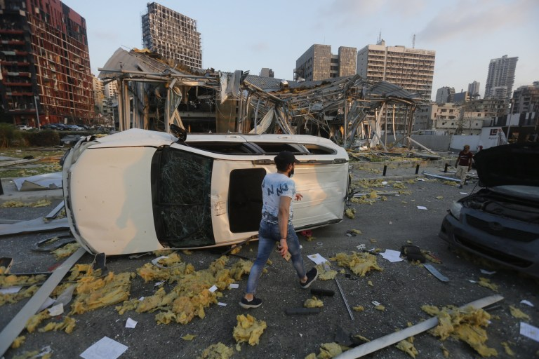 BEIRUT, LEBANON - AUGUST 04: A man walks by an overturned car and destroyed buildings on August 4, 2020 in Beirut, Lebanon. At least 50 people were killed and thousands more injured when two explosions occurred near the Lebanese capital's port area. (Photo by Marwan Tahtah/Getty Images)
