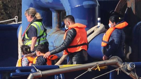 Un officier des forces frontalières escorte une jeune famille que l'on pense être des migrants d'un navire des forces frontalières après leur arrivée à Douvres, dans le Kent, à la suite d'un certain nombre d'incidents de petits bateaux dans la Manche.  Photo PA.  Date de la photo: vendredi 7 août 2020. Voir l'histoire de l'AP POLITIQUE Migrants.  Crédit photo doit se lire: Gareth Fuller / PA Wire