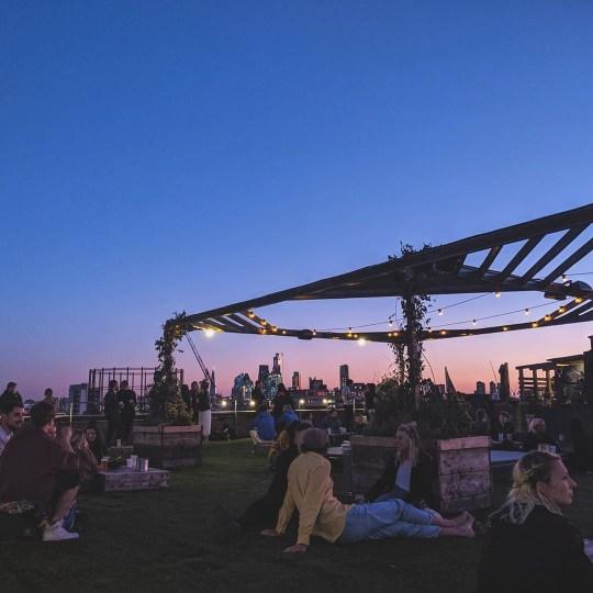 Des gens étaient assis dans un bar sur le toit de Netil 360 au crépuscule