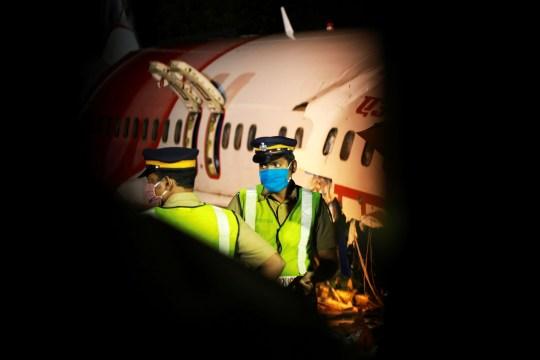 Le personnel de sécurité monte la garde devant l'épave d'un avion d'Air India Express, qui transportait plus de 190 passagers et membres d'équipage de Dubaï, après son écrasement à l'aéroport international de Calicut à Karipur, Kerala, au début du 8 août 2020.